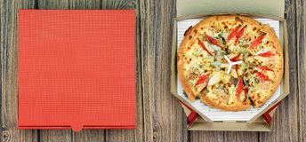 Pizza and the delivery box on wooden background. Stock Photos