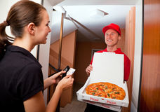 Pizza Delivery. Delivery boy presenting a hot pizza to a female customer at her door Royalty Free Stock Photos