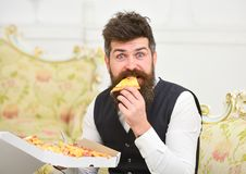 Pizza delivery concept. Man with beard and mustache holds delivered box with tasty fresh hot pizza. Macho in classic. Clothes hungry, on surprised face, holds stock photos