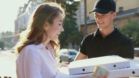 Pizza Delivery. Courier Delivering Box With Food To Client. Woman Paying Order Outdoors stock footage