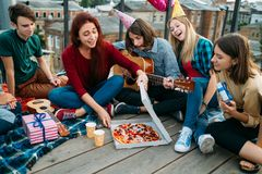 Pizza delivery delicious food hungry teens. Pizza delivery to the rooftop. Unconventional birthday food. Youth eating preferences. Tasty and delicious food Stock Photography
