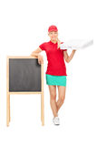 Pizza delivery girl standing by a blank blackboard Stock Images