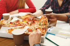 Students learning and eating pizza. Pizza delivery. Happy people eating lunch at coworking office during break, crop, closeup Stock Photo