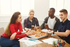 Students learning and eating pizza. Pizza delivery. Happy people eating lunch at coworking office during break. Fast food and team work concept Royalty Free Stock Photos