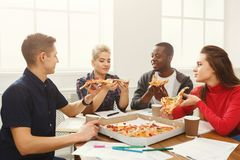 Students learning and eating pizza. Pizza delivery. Happy people eating lunch at coworking office during break. Fast food and team work concept Royalty Free Stock Photography