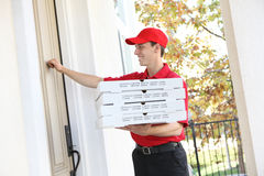 Pizza Delivery Man. A handsome young pizza delivery man holding a pizza stock images