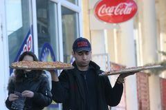 Pizza Delivery Man brings Pizzas on hands in the street of Pernik, Bulgaria – jan 26, 2008 Stock Photo