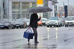 Pizza delivery man carries a pizza bag in right hand and umbrella in left hand. Bad and rainy weather does not prevent him to does his job. Concept of a royalty free stock images