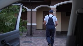 Pizza delivery man carrying boxes to house door. Close-up of bearded worker of food delivery service taking boxes out from car and walking to house door stock footage