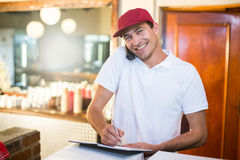 Pizza delivery man taking an order over the phone Royalty Free Stock Photo