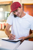 Pizza delivery man taking an order over the phone Stock Image