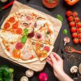 Pizza deliziosa con gli ingredienti e la mano della donna sulla tavola scura Disposizione piana Vista superiore Alimento italiano immagine stock