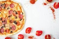 Pizza deliziosa con gli ingredienti e le spezie su fondo rustico bianco Disposizione piana, vista superiore Fotografie Stock Libere da Diritti