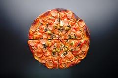 Pizza deliziosa con i funghi e le salsiccie sulla tavola ceramica nera Immagini Stock