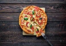 Pizza deliziosa con la forcella sulla fetta Fotografie Stock