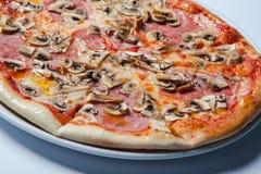 Pizza deliziosa italiana con i funghi ed il prosciutto fotografia stock libera da diritti