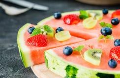 Pizza dell'anguria tagliata con i frutti sul bordo di legno, fine su immagine stock libera da diritti