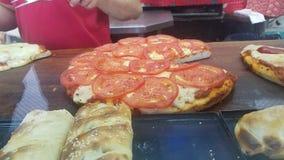 Pizza dell'Argentina coperta in pomodori immagini stock