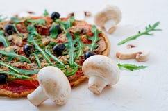 Pizza della verdura con i funghi, pomodori, olive nere, rucola sui precedenti bianchi decorati con i funghi freschi Fotografia Stock