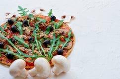 Pizza della verdura con il rucola, pomodori, olive nere sui precedenti bianchi decorati con i funghi freschi Spazio della copia l Immagini Stock