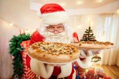 Pizza in den Händen von Santa Claus am Weihnachten, guten Rutsch ins Neue Jahr c Stockfotografie