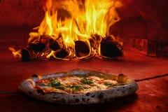 Pizza in den Holzofen mit offenem Feuer Lizenzfreies Stockfoto