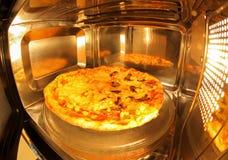Pizza dentro de la microonda Imagenes de archivo