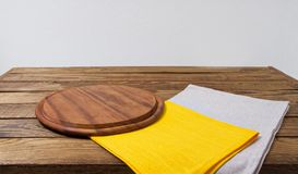 Pizza desk, yellow grow napkins on empty wooden table, copy space.  stock photo