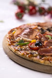 Pizza detail. Pizza on a wooden plate, tomatoes in the background royalty free stock photos