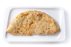 Pizza di Calzone in un piatto rettangolare su un fondo bianco isolato immagine stock