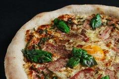 Pizza di Carbonara con la fine dell'uovo e del bacon su su fondo scuro immagini stock