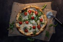 Pizza di formaggio con carta ed il coltello sulla vista superiore del fondo concreto scuro Immagine Stock Libera da Diritti