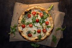 Pizza di formaggio con carta ed il pomodoro sulla vista superiore del fondo di legno scuro Immagini Stock