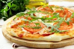 Pizza di Margarita con i pomodori e con arugula fotografia stock