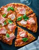 Pizza di merguez casalinga con bacon fresco sopra fondo nero Immagini Stock Libere da Diritti
