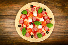 Pizza di merguez cruda con la salsiccia, formaggio, mozzarella, olive e Fotografie Stock