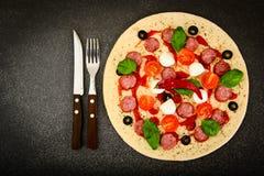 Pizza di merguez cruda con la salsiccia, formaggio, mozzarella, olive e Fotografia Stock