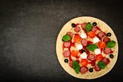 Pizza di merguez cruda con la salsiccia, formaggio, mozzarella, olive e Immagini Stock