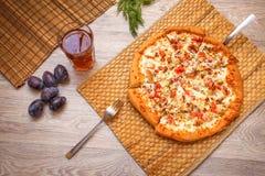 Pizza di recente al forno con una crosta rubiconda, diffusione fuori su una paglia essere immagini stock