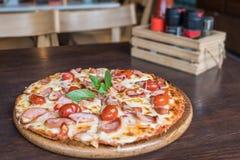 Pizza di salsiccia piccante sulla tavola resturant Fotografie Stock Libere da Diritti