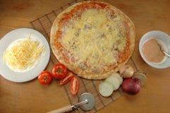 Pizza, die auf der Tabelle liegt Lizenzfreies Stockbild