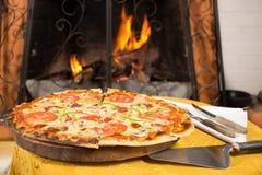 Pizza die een houten oven ingaan stock foto's