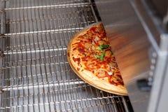 Pizza die in industriële oven worden gebakken stock afbeeldingen