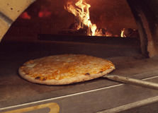Pizza, die in Ofen einsteigt Lizenzfreie Stockfotografie