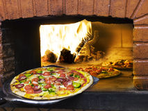 Pizza die uit een houten brandende pizzaoven komt. Royalty-vrije Stock Foto