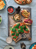 Pizza, different hot dogs, beer and snack for beer. Dinner table concept. Homemade pizza, different hot dogs, beer and snack for beer on rustic table, top view stock photo