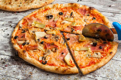 Pizza with different toppings. Italian pizza with different sorts of cheese, vegetables and meat on old wooden background close up Stock Photos