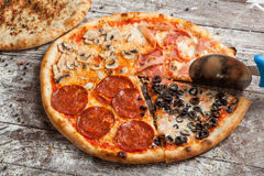 Pizza with different toppings. Italian pizza with different sorts of cheese, vegetables and meat on old wooden background close up Royalty Free Stock Photo