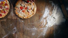 Pizza on dish wooden board Hand cutting with pizza cutter. top view