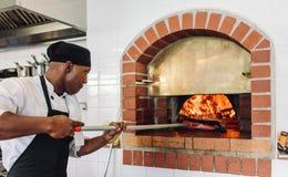 Pizza do cozimento do cozinheiro chefe no forno ateado fogo madeira foto de stock